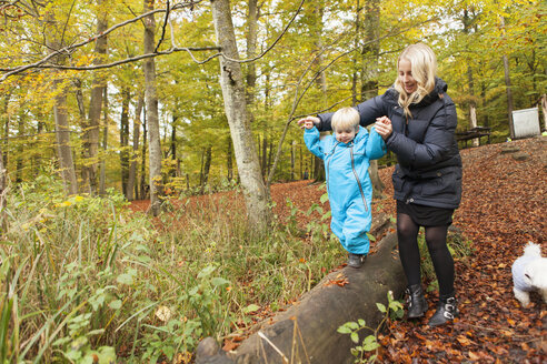 Mother assisting son walking on log - ASTF01324