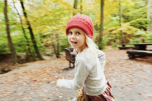 Portrait of happy girl running in forest - ASTF01333
