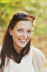 Portrait of happy beautiful young woman in forest - ASTF01351