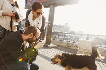 Friends photographing dog on bridge in city - ASTF01369