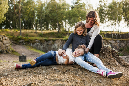 Playful mother and daughters enjoying while sitting in forest - ASTF01396