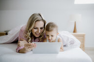 Smiling mother and toddler son lying in bed at home using tablet - HAPF02809