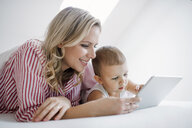 Smiling mother and toddler son lying in bed at home using tablet - HAPF02812