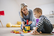 Happy mother and toddler son playing with building blocks at home - HAPF02827