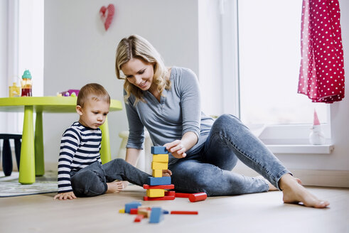Smiling mother and toddler son playing with building blocks at home - HAPF02830