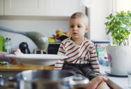 Toddler boy watching mother preparing food in kitchen at home - HAPF02836