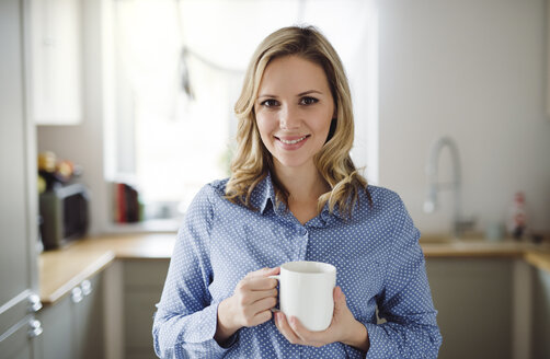 Portrait of smiling woman holding a cup of coffee at home - HAPF02845