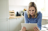Smiling woman using tablet at home - HAPF02848