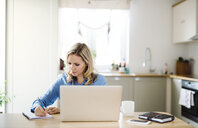 Woman with laptop working at home, taking notes - HAPF02851