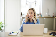 Smiling woman with laptop and cell phone working at home - HAPF02854