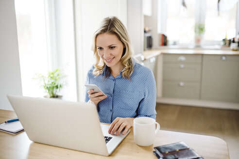Smiling woman with laptop and cell phone working at home - HAPF02857