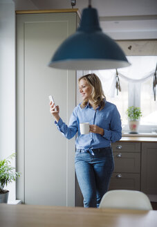 Smiling woman holding a cup of coffee and smartphone at home - HAPF02860