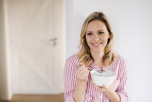 Smiling woman having breakfast in the morning at home - HAPF02866