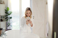 Smiling woman wearing bathrobe in bathroom at home holding cell phone - HAPF02872