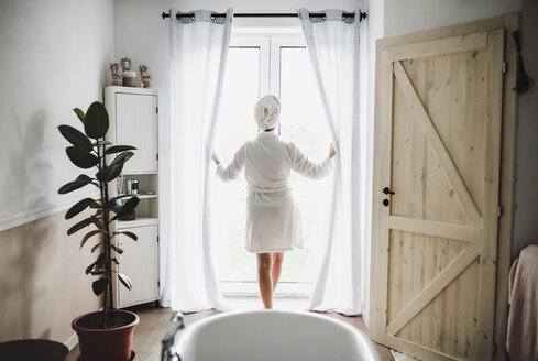 Woman in bathrobe with towel around her head standing at the window at home - HAPF02875