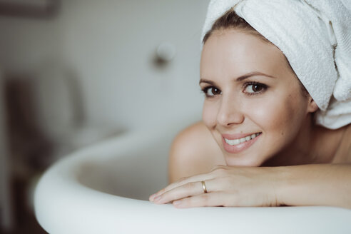 Portrait of smiling woman with towel around her head taking a bath at home - HAPF02878