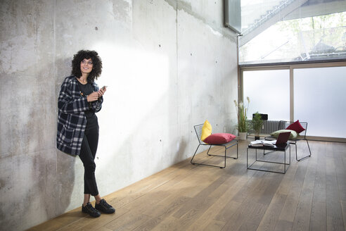 Smiling woman with cell phone leaning against concrete wall in a loft - FKF03148