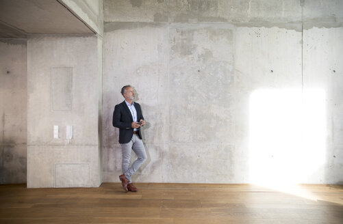 Businessman with cell phone leaning against concrete wall in a loft - FKF03166