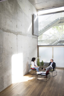 Businessman and businesswoman sitting in a loft at concrete wall talking - FKF03172