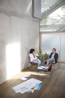 Businessman and businesswoman talking in a loft with documents on the floor - FKF03175