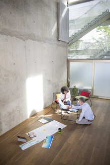 Businessman and businesswoman talking in a loft with documents on the floor - FKF03181