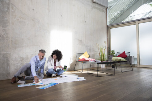Businessman and businesswoman sitting on the floor in a loft discussing documents - FKF03184