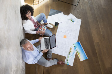 Businessman and businesswoman sitting on the floor in a loft working with laptop and documents - FKF03187