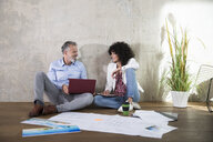 Businessman and businesswoman sitting on the floor in a loft working with laptop and documents - FKF03190