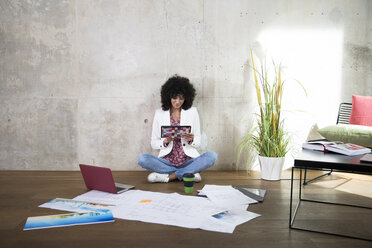 Businesswoman sitting on the floor in a loft using tablet - FKF03193