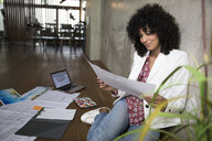 Businesswoman sitting on the floor in a loft working on documents - FKF03202