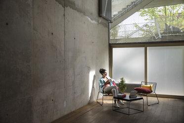 Businesswoman sitting in a loft at concrete wall having a break - FKF03211