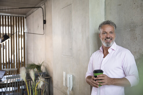 Smiling businessman holding coffee mug at concrete wall in a loft - FKF03214