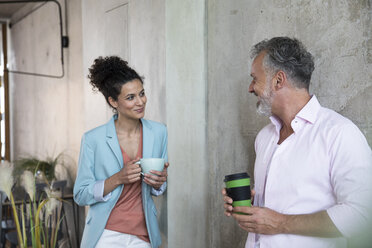 Smiling businessman and businesswoman having a coffee break in a loft - FKF03217