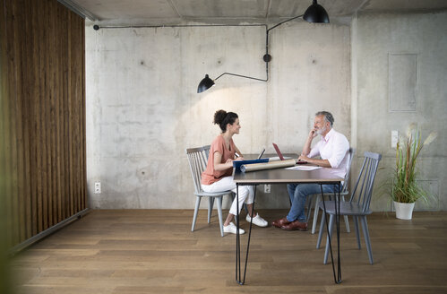 Smiling businessman and businesswoman working at table in a loft - FKF03220