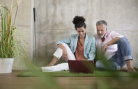 Casual businessman and businesswoman sitting on artificial turf in a loft sharing laptop - FKF03223