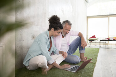 Casual businessman and businesswoman sitting on artificial turf in a loft sharing laptop - FKF03226