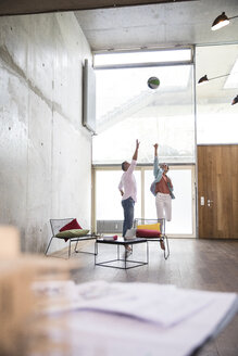 Casual businessman and businesswoman playing basketball in a loft - FKF03229