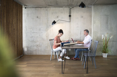 Businessman and businesswoman working at table in a loft - FKF03232