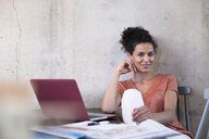 Portrait of smiling businesswoman sitting at table with documents and laptop - FKF03238
