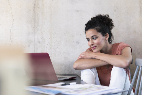 Smiling businesswoman sitting at table with documents and laptop - FKF03241