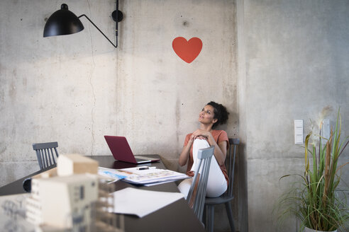 Businesswoman sitting at table in a loft under a heart on concrete wall - FKF03244