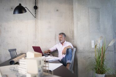 Businessman in a loft using laptop with documents and architectural model on table - FKF03247