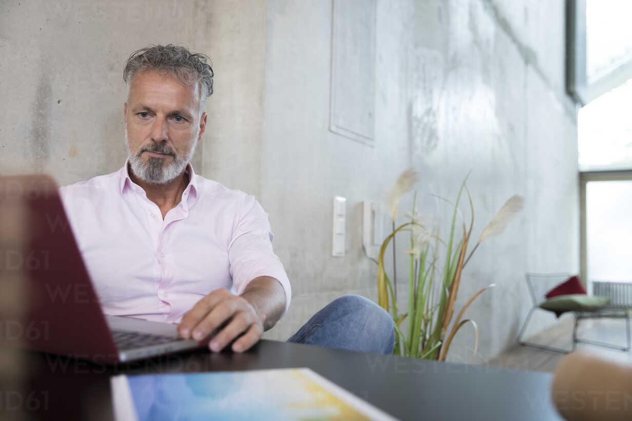 Businessman sitting at table in a loft using laptop - FKF03250 - Florian Küttler/Westend61