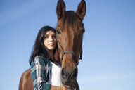 Portrait of woman with horse under blue sky - KBF00379