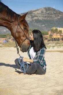 Spain, Tarifa, woman with horse sitting on the beach - KBF00382