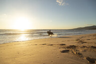 Spain, Tarifa, woman riding horse on the beach at sunset - KBF00388
