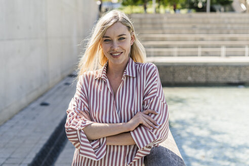 Portrait of smiling blond woman wearing striped shirt - GIOF05456