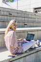 Portrait of smiling young woman with laptop sitting on stairs outdoors watching something - GIOF05459