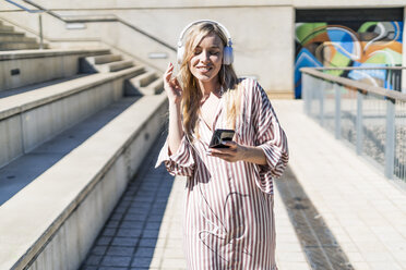 Spain, Barcelona, portrait of smiling young woman using smartphone and headphones outdoors - GIOF05462
