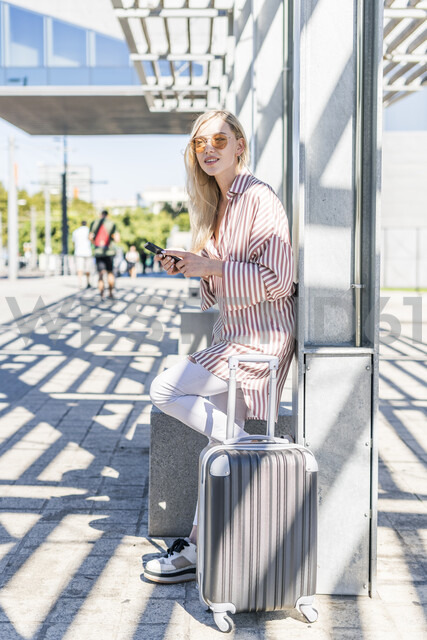 Spain, Barcelona, young woman with trolley bag and cell phone waiting at station - GIOF05468 - Giorgio Fochesato/Westend61